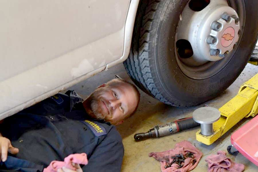 A mechanic smiling from underneath a vehicle in the shop