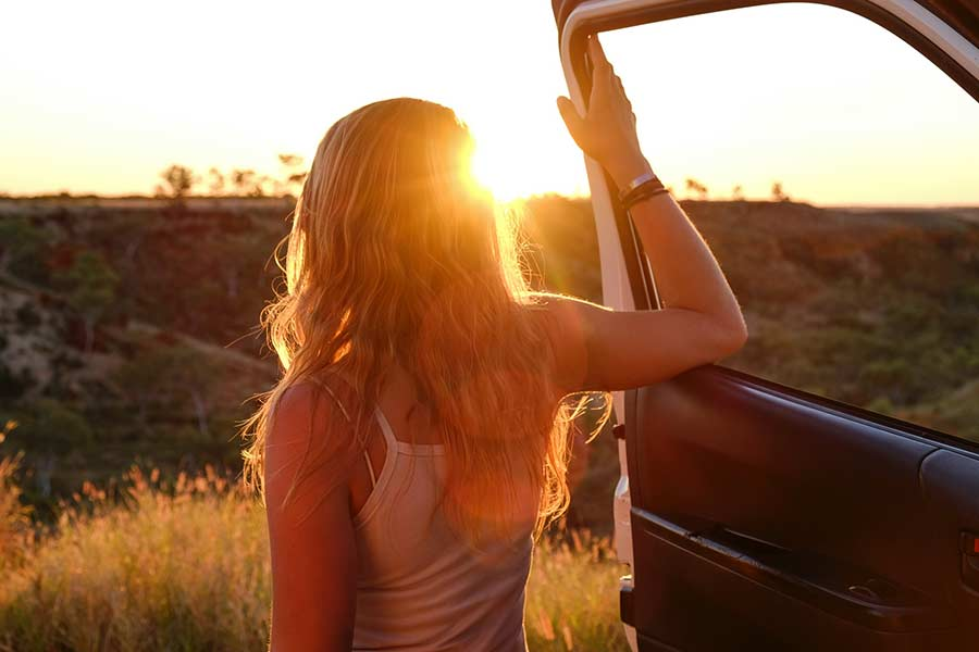 Woman exiting a truck to watch the sun rise on a summer road trip