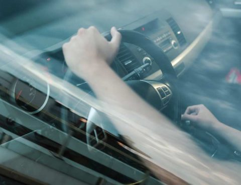 Woman shifting gears while driving