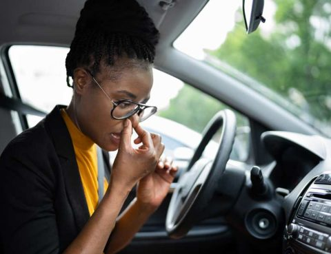Woman holding her nose after starting her car