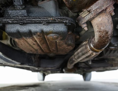 Close-up of the underside of a car, showing an engine oil leak.