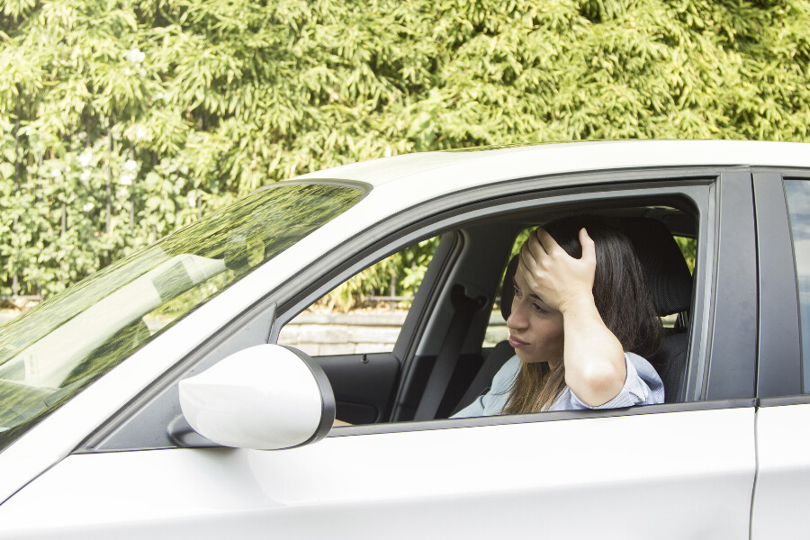 A woman frustrated that her car jerks while accelerating.